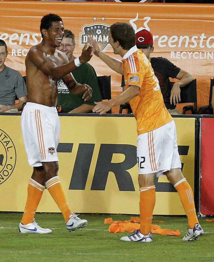 The Houston Dynamo's Carlo Costly left, celebrates teammate Bobby Boswell after Costly scored a goal against the LA Galaxy during the second period at Robertson Stadium Sunday, Oct. 23, 2011, in Houston. Photo: James Nielsen, Chronicle / © 2011 Houston Chronicle