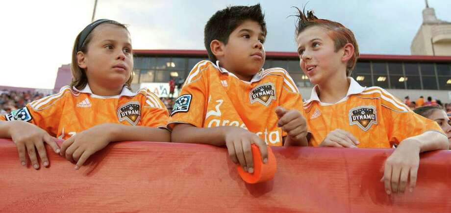 Nine-year-old Albert Bradshaw left, ten-year-old Jean Beaujon and ten-year-old Ben Garvin watch as the Houston Dynamo play the LA Galaxy during the first period in MLS game action at Robertson Stadium Sunday, Oct. 23, 2011, in Houston. Photo: James Nielsen, Chronicle / © 2011 Houston Chronicle