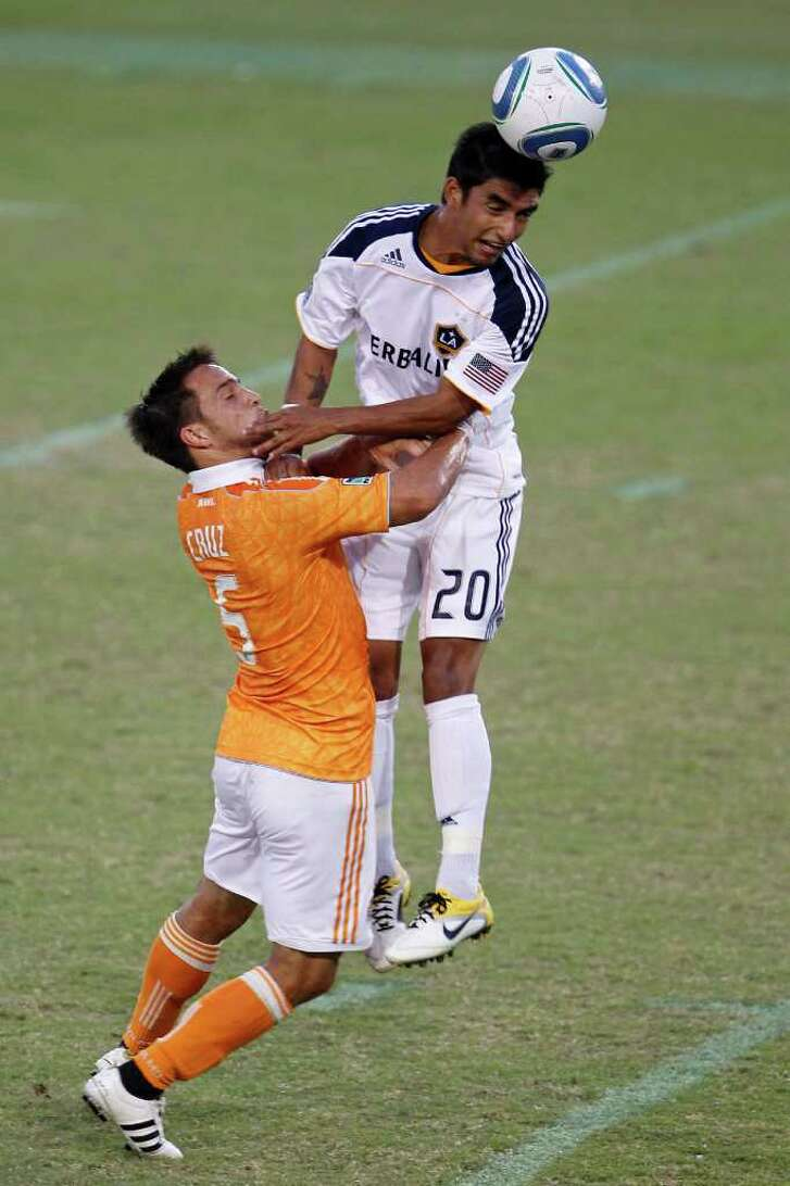 The Houston Dynamo's Danny Cruz collides with A.J. DeLaGarza of the LA Galaxy during the first period of MLS game action at Robertson Stadium Sunday, Oct. 23, 2011, in Houston.
