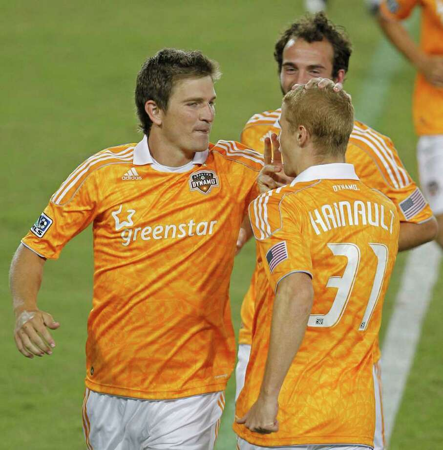 The Houston Dynamo's Bobby Boswell left, celebrates with teammate Andre Hainault right, after Boswell scored a goal against the LA Galaxy during the second period of MLS game action at Robertson Stadium Sunday, Oct. 23, 2011, in Houston. Photo: James Nielsen, Chronicle / © 2011 Houston Chronicle