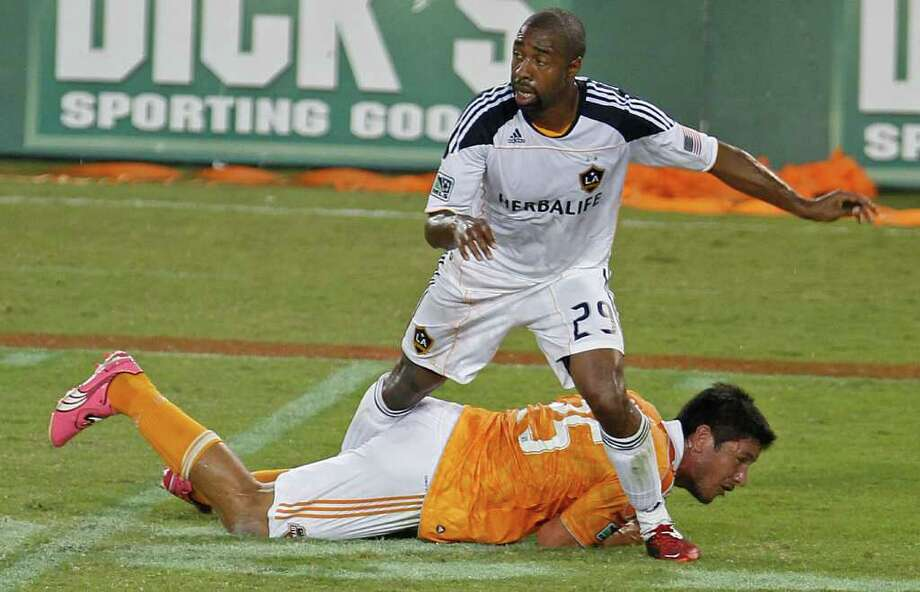 Dasan Robinson of the LA Galaxy stands over the Houston Dynamo's Brian Ching during the first period in MLS game action at Robertson Stadium Sunday, Oct. 23, 2011, in Houston. Photo: James Nielsen, Chronicle / © 2011 Houston Chronicle