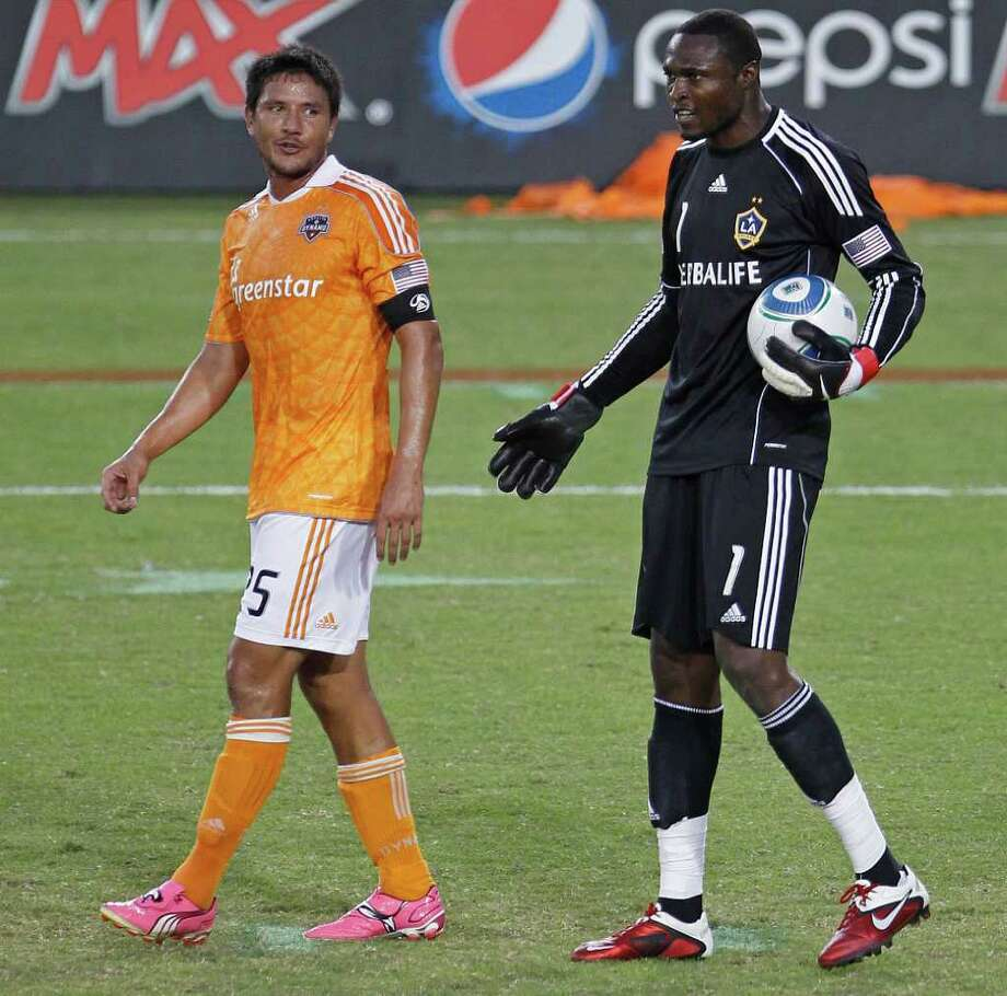 The Houston Dynamo's Brian Ching left, chats with Donovan Ricketts of the LA Galaxy during the first period in MLS game action at Robertson Stadium Sunday, Oct. 23, 2011, in Houston. Photo: James Nielsen, Chronicle / © 2011 Houston Chronicle