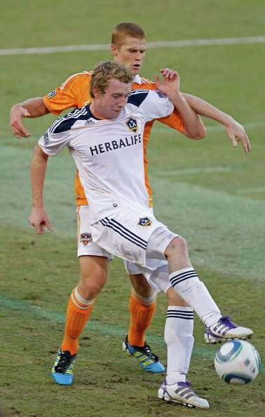 The Houston Dynamo's Andre Hainault tangles with Jack McBean of LA Galaxy during the first period in