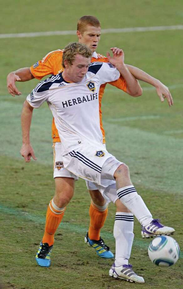 The Houston Dynamo's Andre Hainault tangles with Jack McBean of LA Galaxy during the first period in MLS game at Robertson Stadium Sunday, Oct. 23, 2011, in Houston. Photo: James Nielsen, Chronicle / © 2011 Houston Chronicle