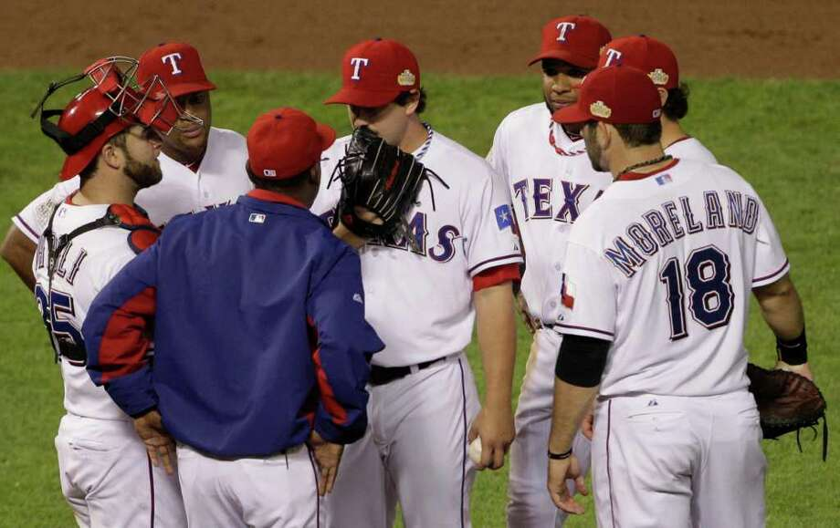 Texas Rangers manager Ron Washington talks to starting pitcher Derek Holland before taking him out of the game during the ninth inning of Game 4 of baseball's World Series against the St. Louis Cardinals Sunday, Oct. 23, 2011, in Arlington, Texas. (AP Photo/Paul Sancya) Photo: Paul Sancya, Associated Press / AP