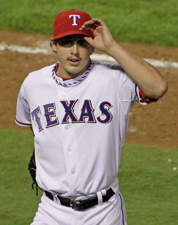 Texas Rangers starting pitcher Derek Holland waves to the crowd after he was taken out of the game during the ninth inning of Game 4 of baseball's World Series against the St. Louis Cardinals Sunday, Oct. 23, 2011, in Arlington, Texas  (AP Photo/Paul Sancya) Photo: Paul Sancya, Associated Press / AP