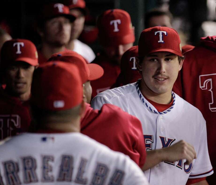 Texas Rangers starting pitcher Derek Holland is congratulated in the dugout after being taken out of the game during the ninth inning of Game 4 of baseball's World Series against the St. Louis Cardinals Sunday, Oct. 23, 2011, in Arlington, Texas. (AP Photo/Charlie Riedel) Photo: Charlie Riedel, Associated Press / AP