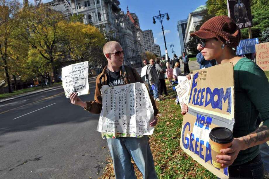 Kat Broadus of Albany, right, and Thomas Lang of Watervliet hold signs along Washington Avenue during the Occupy Albany protest in Academy Park across from the Capitol on Sunday Oct. 23, 2011 in Albany, NY.  Broadus works 7 days a week, and made time to join the protest before returning to work. Lang has been unable to find work.  (Philip Kamrass / Times Union ) Photo: Philip Kamrass