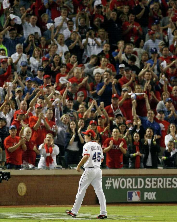 Fans cheer as Texas Rangers pitcher Derek Holland leaves the game during the ninth inning of Game 4 of baseball's World Series against the St. Louis Cardinals, Sunday, Oct. 23, 2011, in Arlington, Texas. (AP Photo/Eric Gay) Photo: Eric Gay, Associated Press / AP