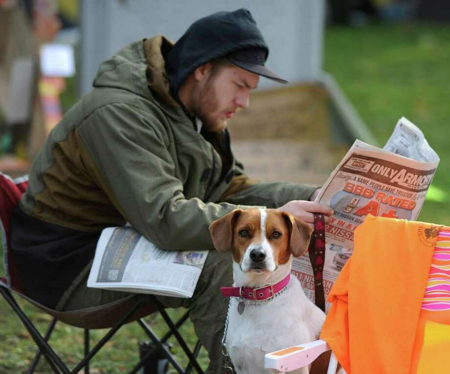 Ben Lacy of Saratoga, with his sidekick Athinia, reads the Times Union at the Occupy Albany encampment in Academy Park in Albany, N.Y. October 24, 2011. Photo: Skip Dickstein / NWest PRS 2011