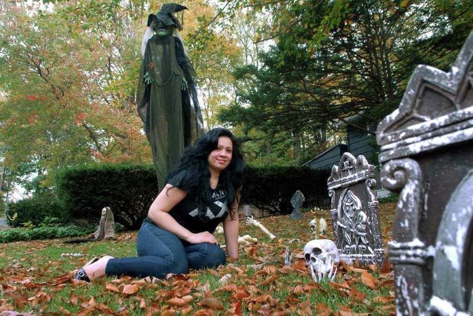 Yvelise Perez sits in on the front lawn of her Clay Hill Rd home in Stamford, Conn. that she decorated for Halloween on Monday October 24, 2011. Photo: Dru Nadler / Stamford Advocate Freelance