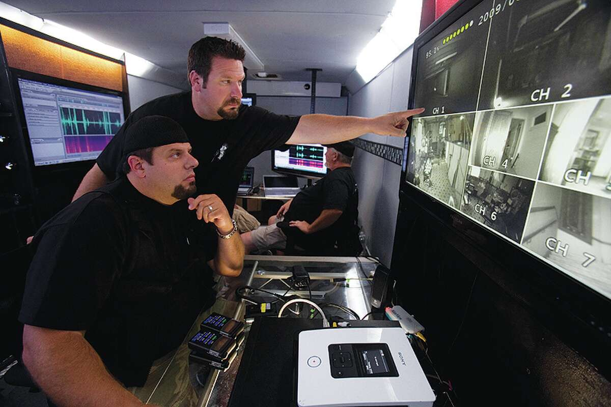 Brothers Brad (front) and Barry Klinge (standing) look at images   inside the Ghost Lab trailer in Chicago.