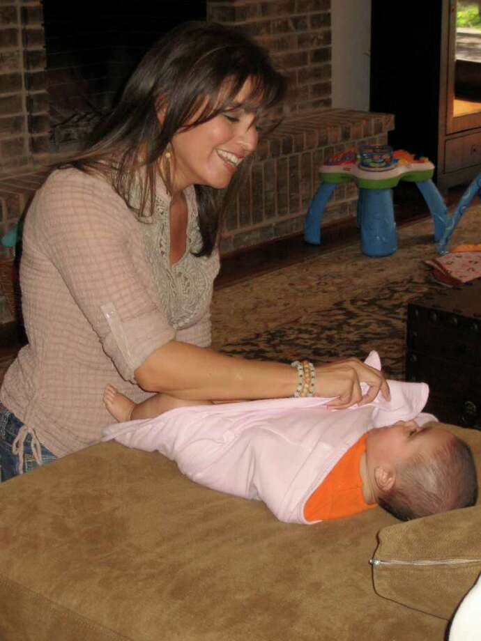 Stacy Bullock holds Elise Halpin, 4 months, to demonstrate techniques and information she provides as part of her business, Stone Oak-based So Real Coaching and Consulting. Photo: Photo By Jenny Halpin