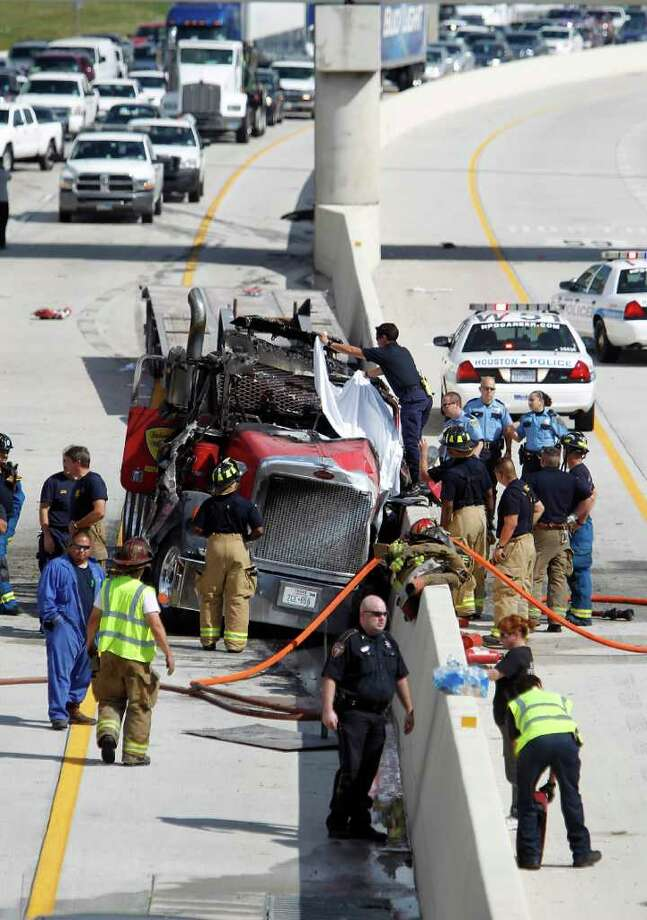 A Houston firefighter pulls a tarp over the drivers side of the burned cab of a tractor-trailer that caught fire on Interstate 10 near San Jacinto Street on Oct. 24, 2011, backing up westbound traffic. The burned rig came to rest on the inside westbound lane near the divider. Photo: Karen Warren / © 2011 Houston Chronicle