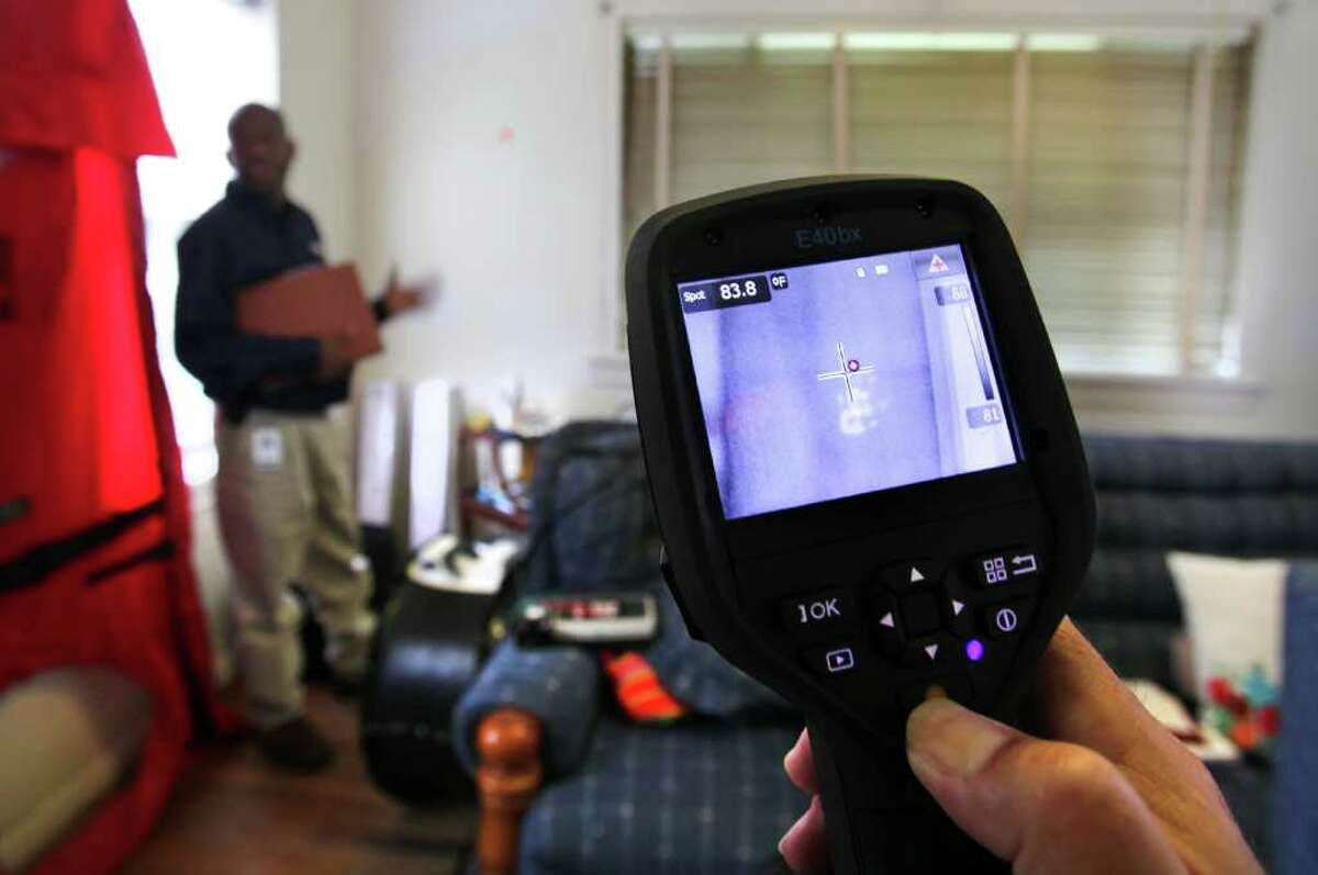 Robert Martinez, Manager for Casa Verde Weatherization, holds a thermal imager camera which shows the heat from the hand print of Kirk Nuckols, Field Representative for CPS, after he removed his hand from the wall. Casa Verde SA marks it's 3000th home to receive weatherization through the program partnered between CPS Energy and the City of San Antonio. The home of Elisa M. Teveni, 83, was the 3000th to receive the benefits of the program. The infrared mark on the wall shows where the device is pointed.