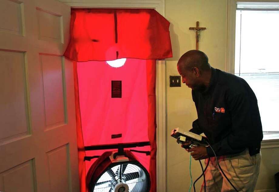Kirk Nuckols, Field Representative for CPS, sets up a blower door to check for air leaks in the home of Elisa M. Teveni.  Casa Verde SA marks it's 3000th home to receive weatherization through the program partnered between CPS Energy and the City of San Antonio.  The home of Elisa M. Teveni, 83, was the 3000th to receive the benefits of the program. Photo: BOB OWEN, SAN ANTONIO EXPRESS-NEWS / rowen@express-news.net