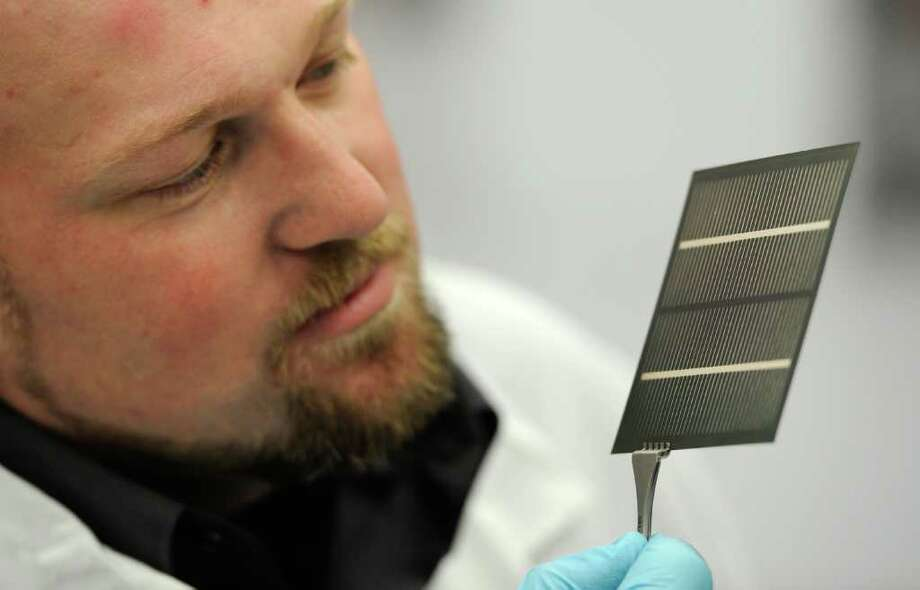 Process Engineer Adam Garney looks over one of the solar cells under production at the Solar Energy Development Center in Halfmoon, N.Y.  October 24, 2011. (Skip Dickstein/Times Union) Photo: Skip Dickstein / 000151094A