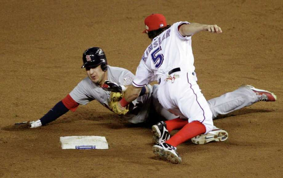 Texas Rangers' Ian Kinsler tags out St. Louis Cardinals' Allen Craig (21) to turn a double play during the ninth inning of Game 5 of baseball's World Series Monday, Oct. 24, 2011, in Arlington, Texas. The Rangers won 4-2 to take a 3-2 lead in the series. (AP Photo/Tony Gutierrez) Photo: Tony Gutierrez, Associated Press / AP