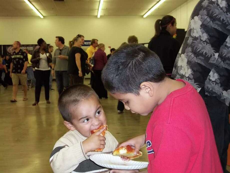 "Brothers Rigo and Frankie Espinoza sink their teeth into some Mr. Gatti's pizza during ""Taste of the Metrocom: 1960s Beach Party"" Oct. 19 at the Live Oak Civic Center. Photo: Photo By Tamara Pearis"