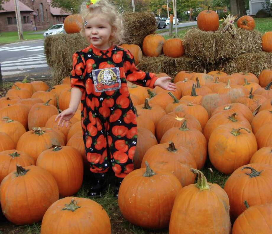 Lucy Jay, 2½, wears a pumpkin jumpsuit while wandering through the pumpkin patch in front of St. Paulís Episcopal Church, which was filled Sunday with about 200 pumpkins for stenciling and carving at the church's annual carving program. Photo: Meg Barone / Fairfield Citizen freelance