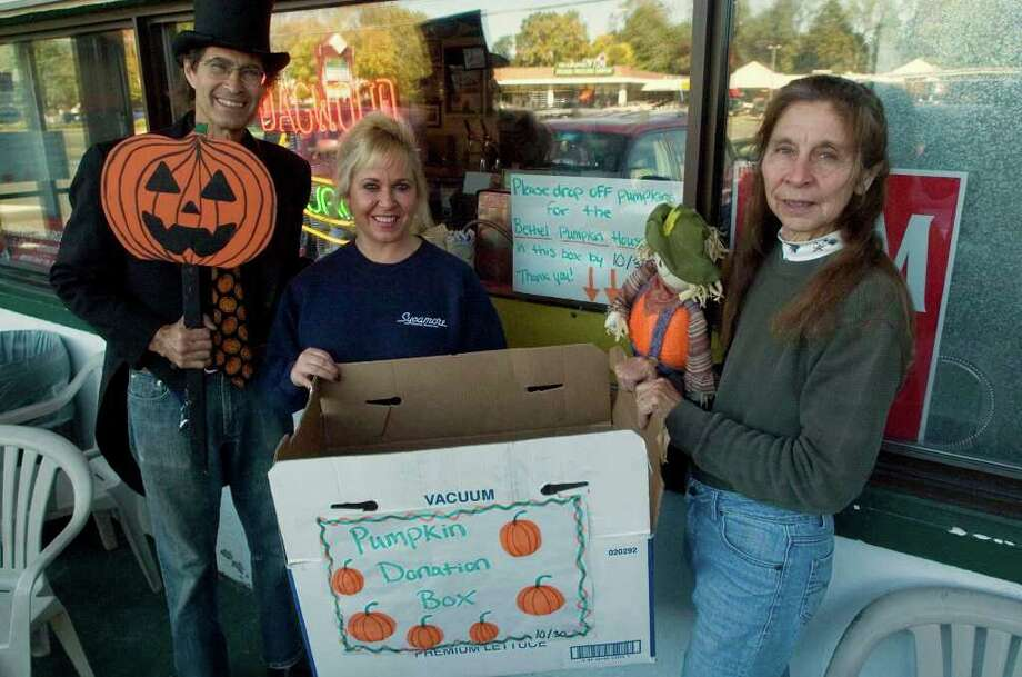 Billy Michael, Kathy Austin, and Billy's wife, Rosaly Donofrio, right, pose in front of Sycamore Diner in Bethel on Tuesday, Oct. 25, 2011. Because of the local pumpkin crop failure due to Tropical Storm Irene, Michael and Donofrio teamed up with the diner to gather donations of carved or uncarved pumpkins for the pumpkin festival they hold at their home on Fleetwood Avenue in Bethel. Photo: Jason Rearick / The News-Times