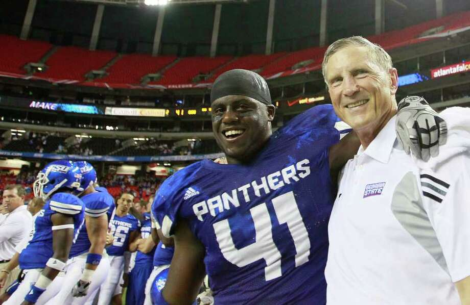 Georgia State coach Bill Curry and Olufemi Opanubi enjoy a happy moment after the program's inaugural victory in 2010. Photo: Kevin C. Cox, Getty Images / 2010 Getty Images