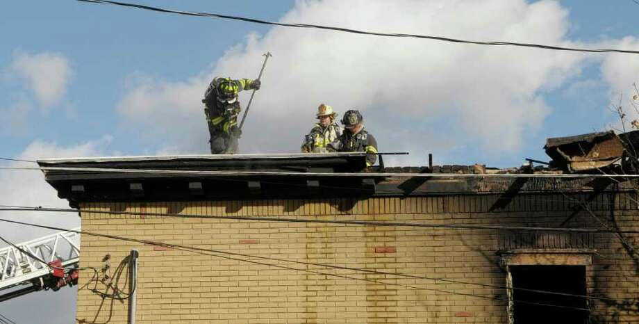 Firefighters work at the scene of an apartment fire at the corner of Hamilton St. and Hamilton Place on Tuesday afternoon, Oct. 25, 2011 in Cohoes.  Cohoes Fire Chief, Joe Fahd said that the fire stared in a second floor apartment and that firefighters from Green Island, Troy and Watervliet were called in to help Cohoes firefighters. (Paul Buckowski / Times Union) Photo: Paul Buckowski