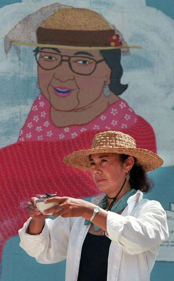 Muralist Terry Ybanez blesses the mural she painted onto the exterior of a laundromat during an unveiling ceremony in South San Antonio Sunday, July 25, 1999. Ybanez erected the mural honoring Emma Tenayuca who died Friday. Teneyuca became famous in 1938 for her efforts to organize pecan shellers for better wages and civil rights. Photo: KRISTA NILES, AP / EXPRESS-NEWS