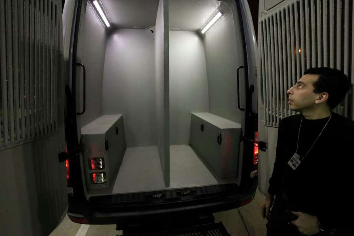 """HPD evidence technician Juan Cejas shows the male and female holding areas in HPD's """"BAT"""" van, a mobile booking and testing unit for alcohol-related offenses."""