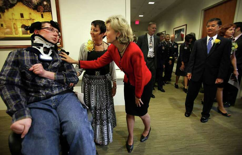 Senator Kay Bailey Hutchison, center, greets U.S. Army Spc. (retired)Chris Harmon 27, left, after she gave her corsage to Chris's mother Cinde Harmon, center left, as Secretary of Veterans Affairs Eric K. Shinseki, right, looks on.  The dignitaries were at the dedication ceremony of the Polytrauma Rehabilitation Center which is in the South Texas Veterans Health Care System. Harmon was the victim of a drunk driving accident in September of 2004 when he was home on a three-day pass.  Tuesday, Oct. 25, 2011.  Photo Bob Owen/rowen@express-news.net Photo: BOB OWEN, SAN ANTONIO EXPRESS-NEWS / rowen@express-news.net