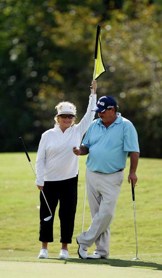 "Victor Leoni stands with his ""caddy"", his mother Rene Leoni, as they wait on the 18th green during the first of four days of Champions Tour Q School at the Woodforest Golf Club, Oct. 25, 2011, in Montgomery. Photo: Karen Warren, Houston Chronicle / © 2011 Houston Chronicle"