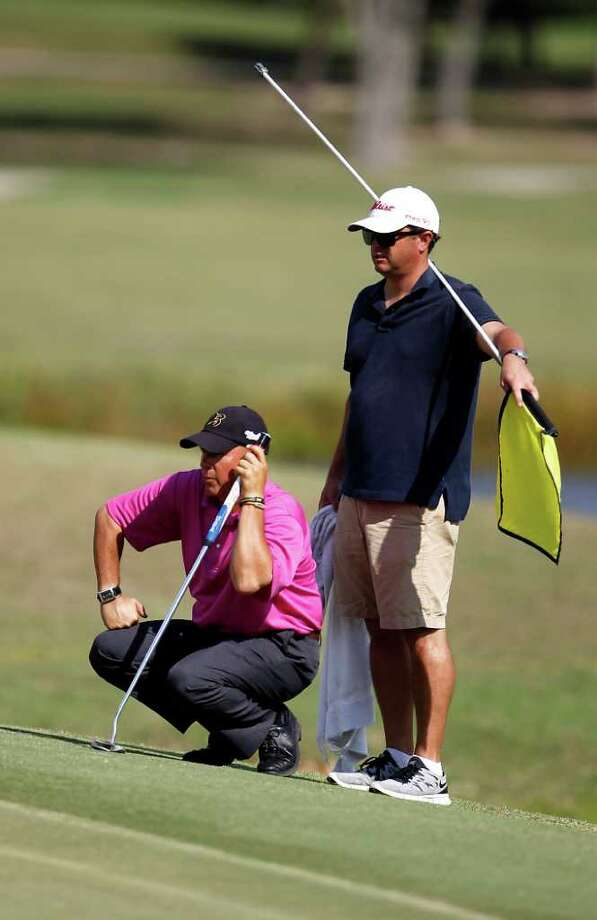 Vic Wilk lines up his putt on 18, as his caddy Greg LaBelle holds the flag during the first of four days of Champions Tour Q School at the Woodforest Golf Club, Oct. 25, 2011, in Montgomery. Photo: Karen Warren, Houston Chronicle / © 2011 Houston Chronicle