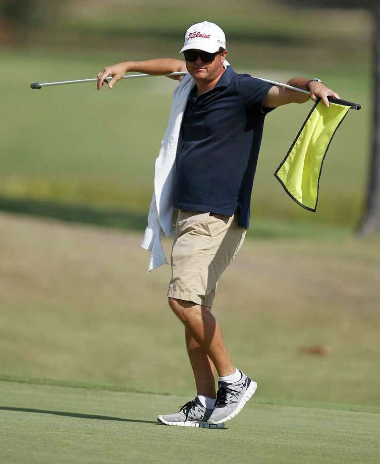 Caddy Greg LaBelle holds the 18th hole flag as he waits for his golfer, Vic Wilk, during the first of four days of Champions Tour Q School at the Woodforest Golf Club, Oct. 25, 2011, in Montgomery. Photo: Karen Warren, Houston Chronicle / © 2011 Houston Chronicle