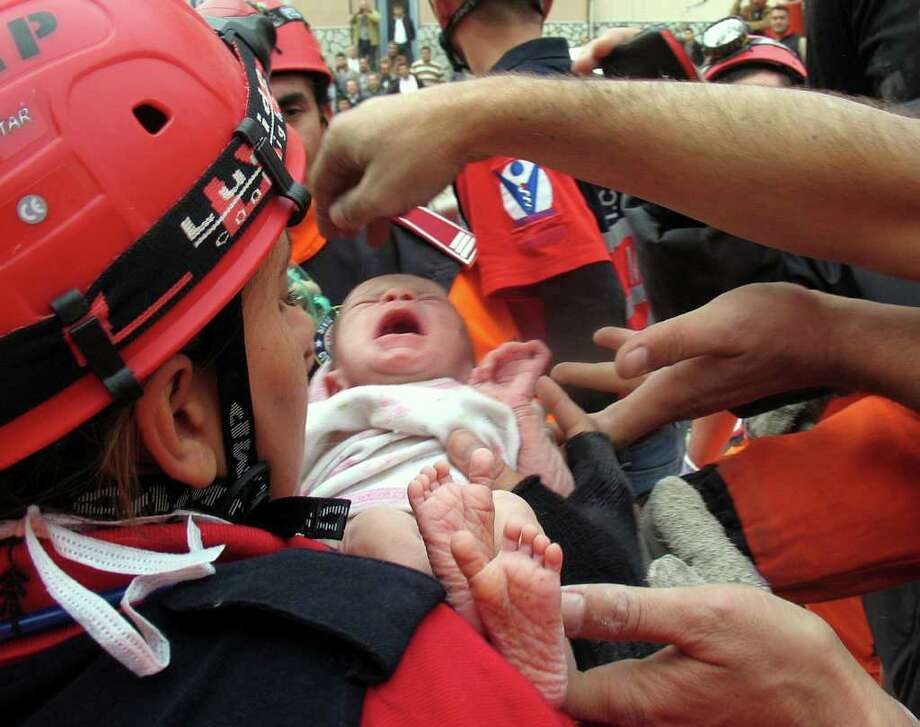 A 2-week-old baby girl was pulled alive from the rubble of an apartment building and rescue workers struggled to save her mother, nearly 48 hours after a 7.2-magnitude earthquake that toppled some 2,000 buildings in eastern Turkey, Ercis, Van, Turkey, on October 25, 2011. Rescuers in orange jumpsuits clapping as the baby, Azra Karaduman, was removed from the wreckage. The baby's mother, Semiha, was still alive, pinned next to a sofa inside the flattened building. Photo: Cem Ozdel, McClatchy-Tribune News Service / Abaca Press