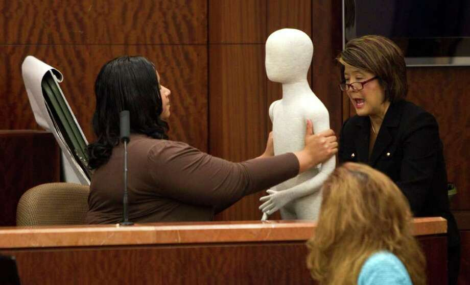 BRETT COOMER : CHRONICLE ON THE STAND: Keyanna Jackson, left, demonstrates the shaking of her son, Kendrick Jackson, during testimony in the murder trial against Roderick Fountain on Tuesday, Photo: Brett Coomer / © 2011 Houston Chronicle