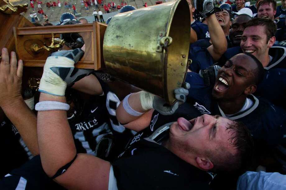 Rice Owls players, including defensive tackle John Gioffre (55), bottom, celebrate with the Bayou Bucket trophy after defeating the Houston Cougars in an NCAA football game at  Rice Stadium on Saturday, Oct. 16, 2010, in Houston. Rice won the game against their cross town rivals by a score of 34-31. Photo: Smiley N. Pool, Houston Chronicle / Houston Chronicle