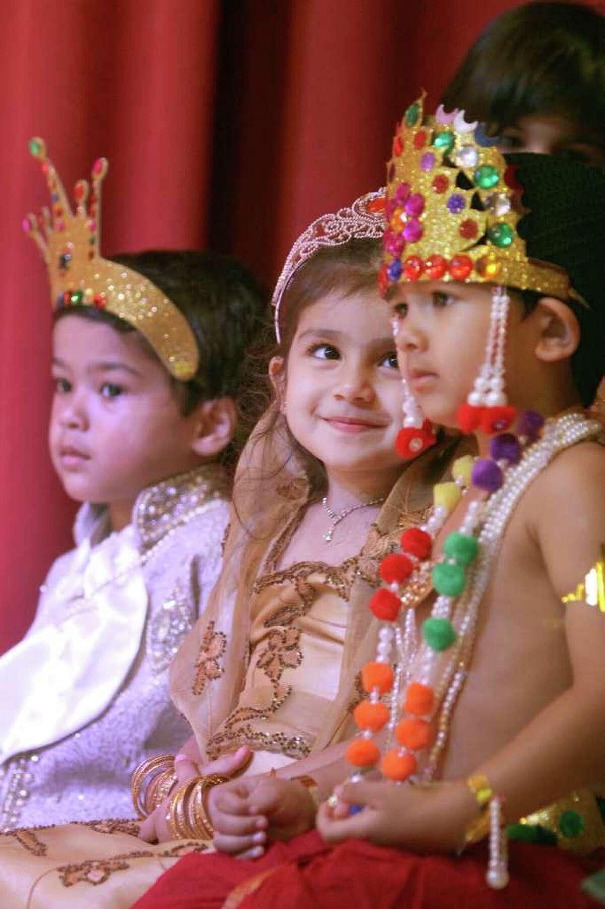 Aanya Malik 3, (center) looks up at Kuber Nilgiri 3 (right) during a children's program at the celebration of Diwali, The Festival of Lights at the Arya Samaj Greater Houston Culture Center on Saturday, October 22, 2011. On left is Neel Chhetri 3. (Alan Warren, For the Chronicle)