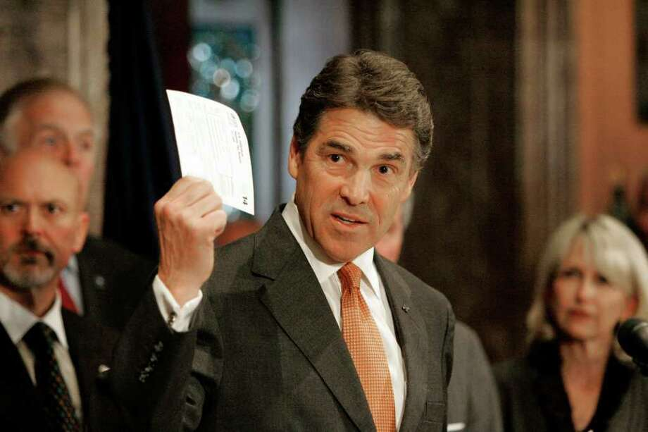 Republican presidential candidate Texas Gov. Rick Perry holds up his version of the tax form that American's would fill out as he outlined a broad economic proposal of a flat 20 percent income tax rate during a news conference Tuesday, Oct. 25, 201, at the State House in Columbia, S.C. (AP Photo/Mary Ann Chastain) Photo: Mary Ann Chastain