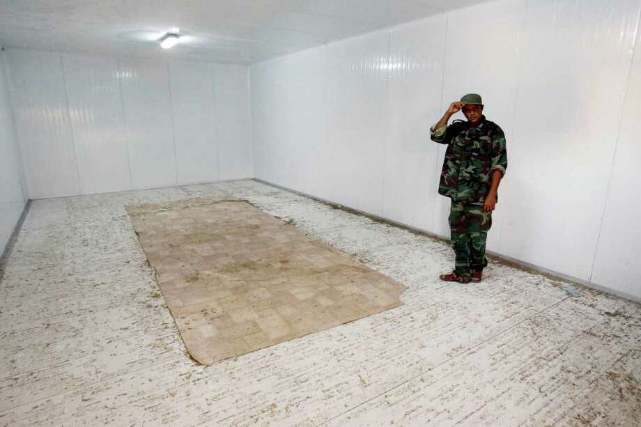 A Libyan revolutionary fighter stands in the empty freezer in a commercial center, where the body of Libyan dictator Moammar Gadhafi was displayed in Misrata, Libya, Tuesday Oct. 25, 2011. The bodies of Moammar Gadhafi, his son, Muatassim Gadhafi, and his ex-defense minister Abu Bakr Younis were removed during the night to be buried in a secret location. (AP Photo/Francois Mori) Photo: Francois Mori / AP