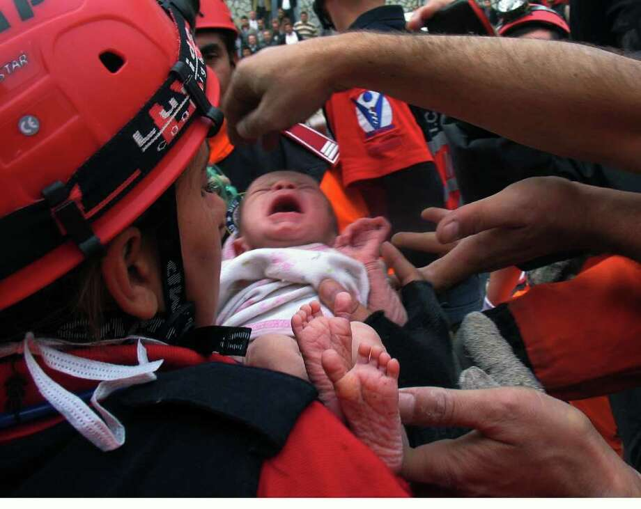 Turkish rescuers carry Azra Karaduman, a two-week-old baby girl they have saved from under debris of a collapsed building in Ercis, Van, eastern Turkey, Tuesday, Oct. 25, 2011. Hundreds of people were killed Sunday after a powerful quake in eastern Turkey. (AP Photo) / AP