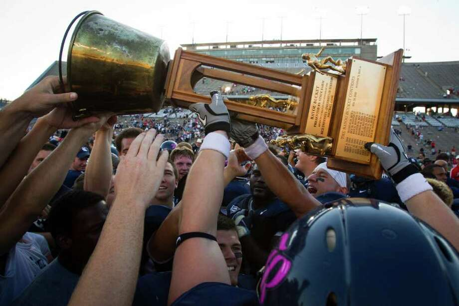 Rice Owls players celebrate with the Bayou Bucket trophy after defeating the Houston Cougars in an NCAA football game at  Rice Stadium on Saturday, Oct. 16, 2010, in Houston. Rice won the game against their cross town rivals by a score of 34-31. ( Smiley N. Pool / Houston Chronicle ) Photo: Smiley N. Pool / Houston Chronicle