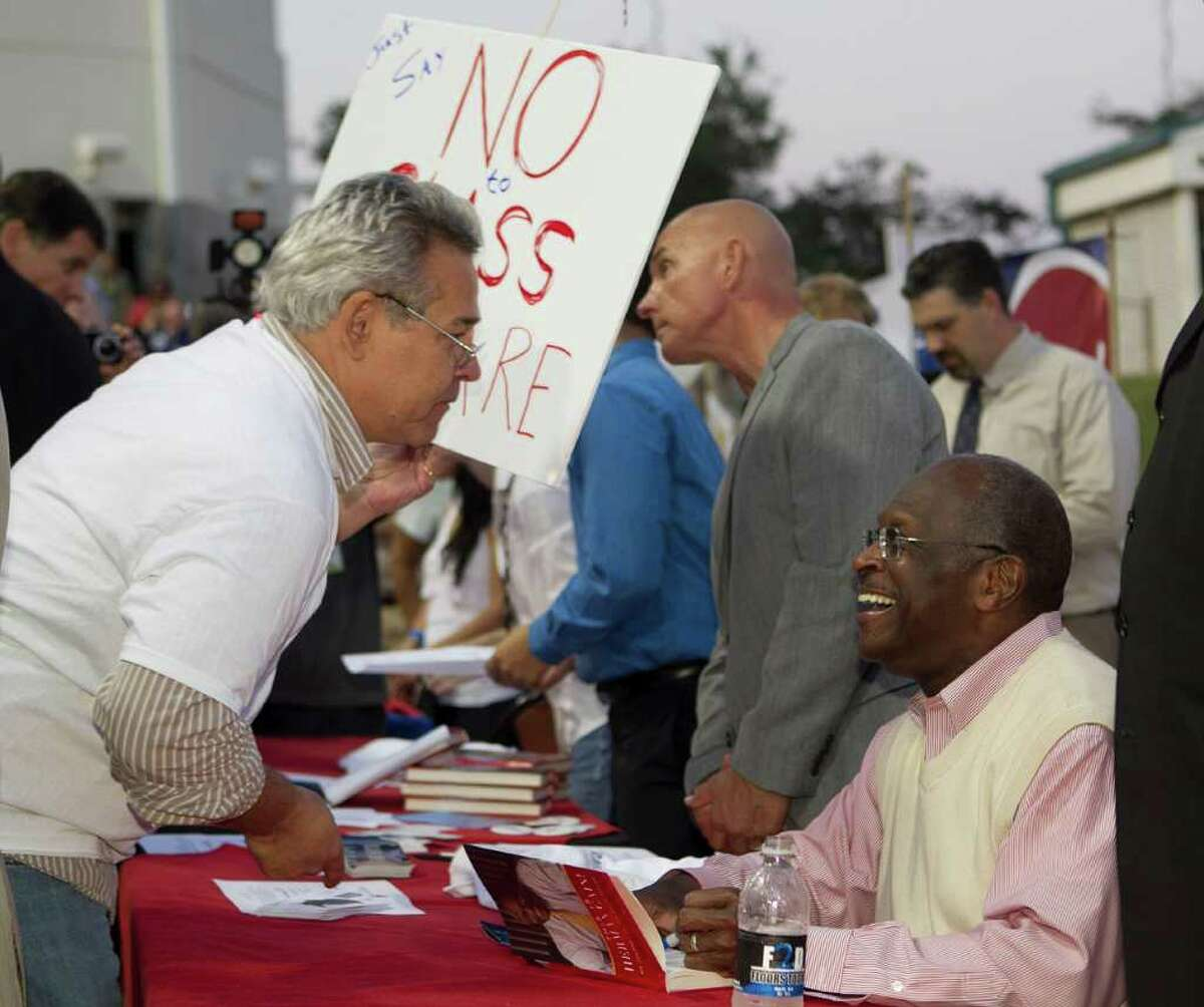 JAMES NIELSEN : CHRONICLE FRONTRUNNER: Presidential candidate Herman Cain signs his new book - This is Herman Cain! My Journey to the White House - for Herman Jacobs during a political rally and book signing event Tuesday night at Gulf Greyhound Park in La Marque.