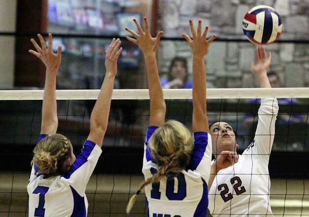 Madison's Jessika Jernigan (22) attempts to hit past MacArthur's Shannon Porter (07) and Claire Scharper (10) in volleyball at Littleton Gym on Tuesday, Oct. 25, 2011. MacArthur defeated Madison in 5 games to knock out Madison from the playoffs. Photo: Kin Man Hui, Kin Man Hui/San Antonio Express-News / San Antonio Express-News