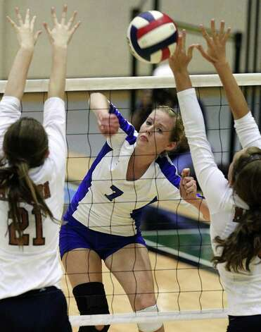 MacArthur's Shannon Porter (07) hits through Madison blockers Victoria Galbraith (21) and Remington Geffken (06) in volleyball at Littleton Gym on Tuesday, Oct. 25, 2011. MacArthur defeated Madison in 5 games to knock out Madison from the playoffs. Photo: Kin Man Hui, Kin Man Hui/San Antonio Express-News / San Antonio Express-News