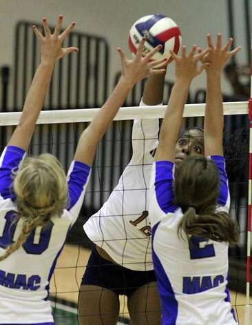 Madison's Tanesha Johnson (12) hits into the awaiting hands of MacArthur blockers Claire Scharper (10) and Dana Moore (02) in volleyball at Littleton Gym on Tuesday, Oct. 25, 2011. MacArthur defeated Madison in 5 games to knock out Madison from the playoffs. Photo: Kin Man Hui, Kin Man Hui/San Antonio Express-News / San Antonio Express-News