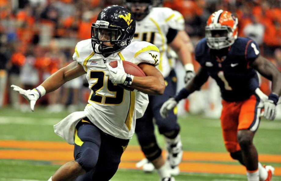 West Virginia's Dustin Garrison (29) runs in the open field against Syracuse during the first quarter of an NCAA college football game in Syracuse, N.Y., on Friday, Oct 21, 2011. Photo: Kevin Rivoli/Associated Press