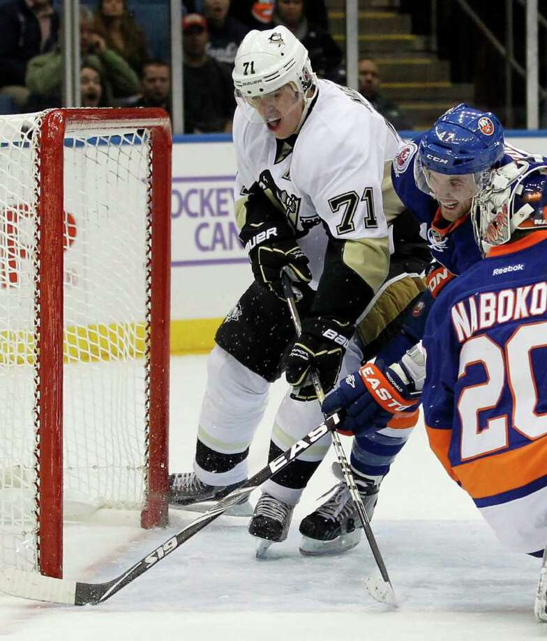 Pittsburgh Penguins' Evgeni Malkin (71) is checked by New York Islanders' Andrew MacDonald, right rear, as he tries to get the puck from MacDonald as they skate through the goal crease during the first period of an NHL hockey game at Nassau Coliseum in Uniondale, N.Y., Tuesday, Oct. 25, 2011. The Penguins won 3-0. (AP Photo/Paul J. Bereswill) Photo: Paul Bereswell