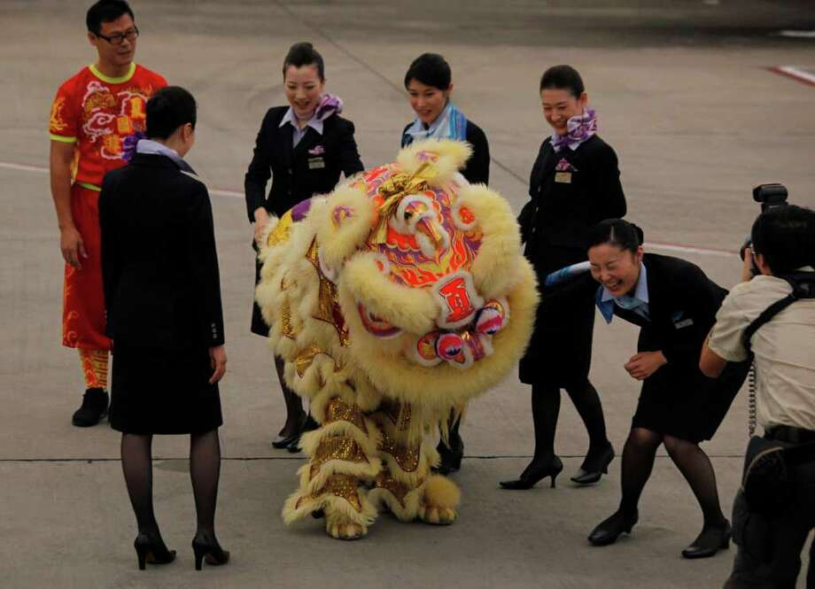 Flight attendants of an All Nippon Airways Boeing 787 react during a lion dance performance after the plane lands at Hong Kong International Airport on the airplane's inaugural commercial flight from Japan, on Wednesday. The jet, nicknamed The Dreamliner by Boeing, was flown by Japan's All Nippon Airways and was packed with aviation reporters and enthusiasts — some of whom paid thousands of dollars for the privilege. Photo: AP