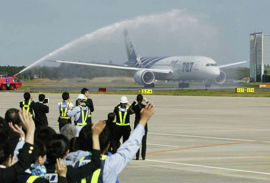 All Nippon Airways staff and others wave at an ANA Boeing 787 taxing on the runway, being sprayed water to celebrate the new airplane's inaugural commercial flight to Hong Kong at Narita International Airport in Narita, east of Tokyo, on Wednesday. (AP Photo/Kyodo News)  Photo: AP