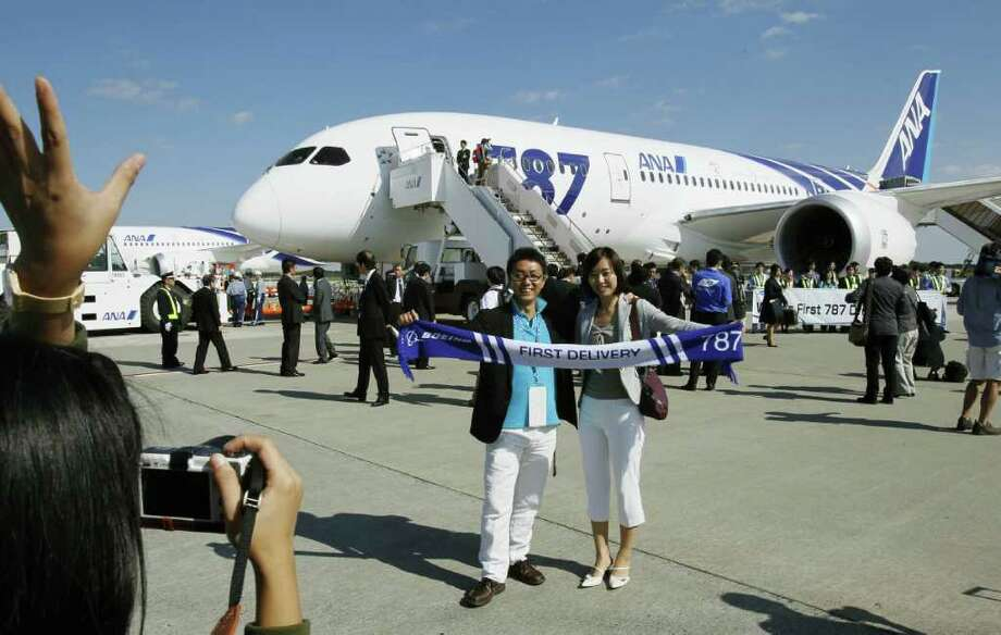 A couple pose for a souvenir photo before boarding an All Nippon Airways Boeing 787 to fly to Hong Kong, marking the airplane's inaugural commercial flight at Narita International Airport in Narita, east of Tokyo, on Wednesday. (AP Photo/Kyodo News) Photo: AP